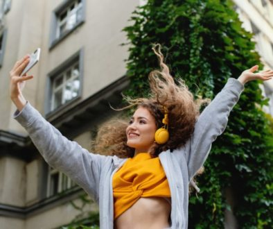 Young woman with smartphone dancing outdoors on street, tik tok concept.